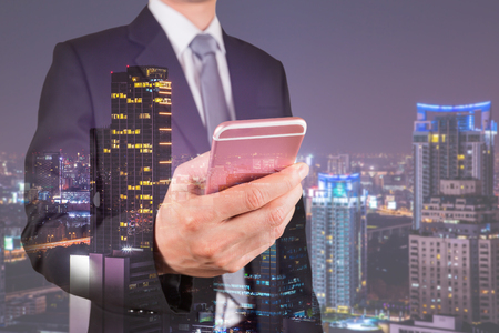 Double exposure of businessman use smartphone, communication 4G 5G node networking telephone cellsite and cityscape urban in the night as business, technology and telecom concept