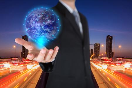 Geschäftsmann, der den leuchtenden Hologramm-Digital-Globus auf der Straße der Lichtspuren hält, in der Nacht städtisch als Geschäfts-, Innovations-, Intelligent- und Ideenkonzept. Elemente dieses von der NASA bereitgestellten Bildes Standard-Bild