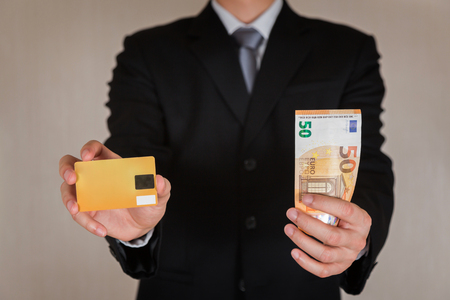 Businessman hold 50 EURO (EUR) money and credit card as business, trade, currency, investment and income concept