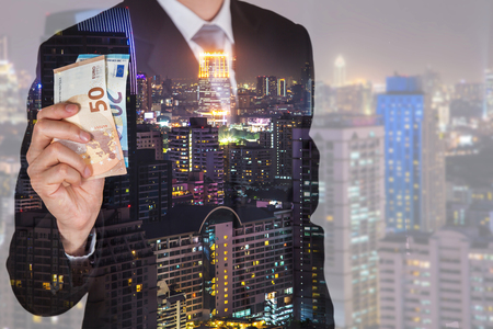 Double exposure of businessman hold EURO (EUR) money and night city as business, trade, currency, investment and income concept 版權商用圖片 - 108318189
