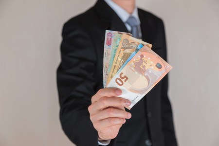 Businessman hold United Arab Emirates Dirham (AED) money as business, trade, investment and income concept Stock Photo