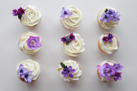 purple flowers: Homemade purple freesia flowers on vanilla cupcakes with whipped cream frosting Stock Photo