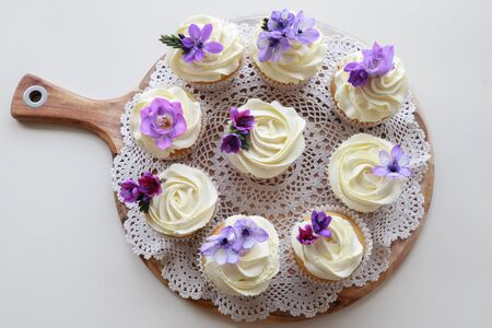 edible: Homemade purple freesia flowers on vanilla cupcakes with whipped cream frosting Stock Photo