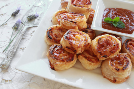 mini pizza: Homemade Hawaiian pizza rolls on white serving plate with tomato sauce