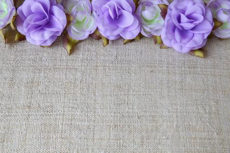 artificial flowers: Artificial purple flowers on linen, copy space background, selective focus
