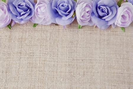blanca y rosa flores artificiales en el lino se levantó, copiar fondo de espacio, el enfoque selectivo, el tono de la vendimia