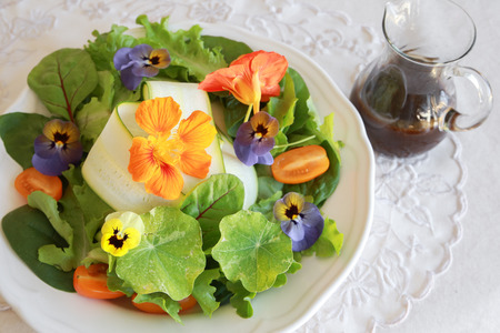 salad plate: Ensalada verde fresca con flores comestibles en blanco plato de servir