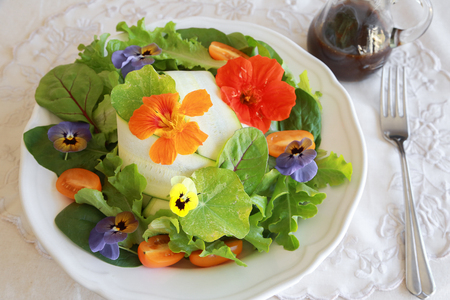 edible: Fresh green salad with edible flowers in white serving dish Stock Photo
