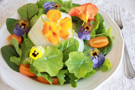 serving dish: Fresh green salad with edible flowers in white serving dish Stock Photo