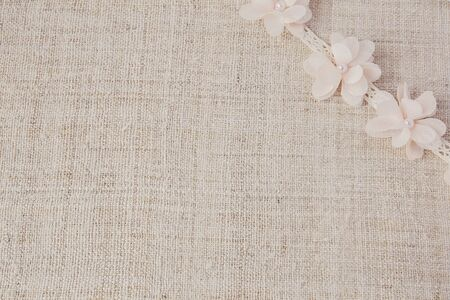 textiles texture: Artificial flowers and lace on linen, copy space background, selective focus, vintage tone