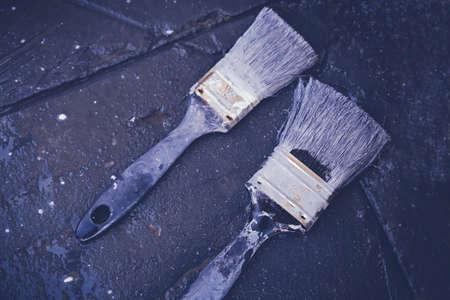 paintbrushes: Used paintbrushes on black patio floor, soft selective focus, toning