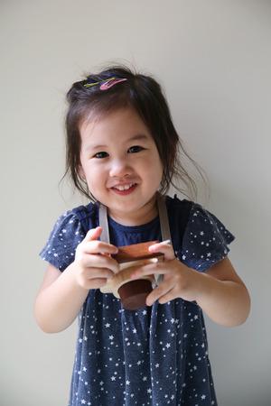 niñas chinas: una chica linda que sostiene el juguete de madera de la cámara, el enfoque selectivo suave