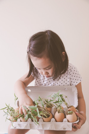 A toddler girl holding and kissing young plants in eggshell, eco concept Stock Photo