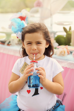 drink me: Cute girl drinking The Drink Me potion, Alice in wonderland tea party theme,toning Stock Photo