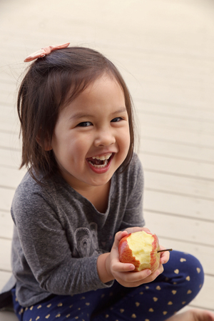 eating fruits: happy girl ands holding a red bitten apple,health concept, toning