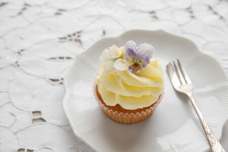 sugared: yellow cupcakes with  sugared edible flowers on vintage plate