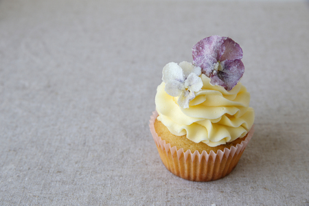 sugared: Yellow cupcakes with purple sugared edible flowers on linen copy space background
