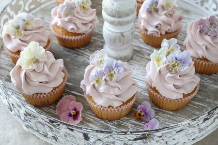 sugared: Purple cupcakes with sugared edible flowers on vintage cake stand Stock Photo