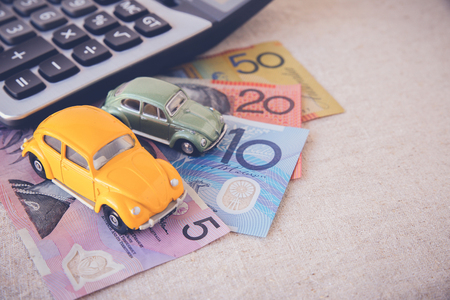 australian money: Toy cars with AUD Australian money and calculator, copy space toning background for car insurance, car Loan,Car business concept