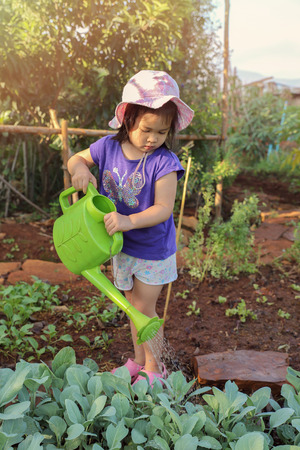 montessori: Little girl using watering can water plants in garden, montessori education concept Stock Photo