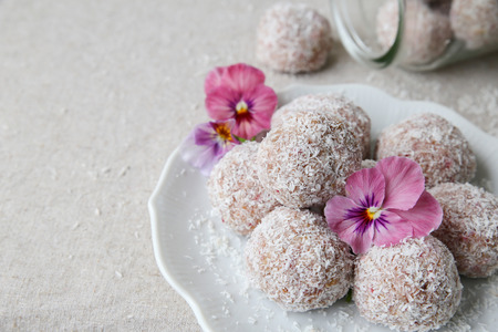 Homemade strawberry, date, cashew and coconut bliss ball with edible flowers Stock Photo