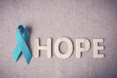 pap smear: Teal Ribbon with HOPE wooden letters, toning, Ovarian Cancer, cervical Cancer, Kidney Cancer awareness Stock Photo