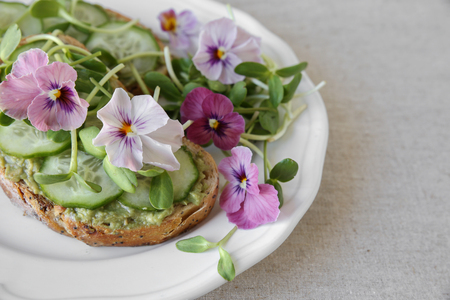 avocado , cucumber, sunflower sprout and edible flowers on sourdough toasts