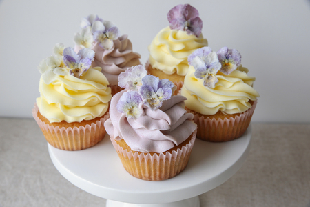Purple and yellow cupcakes with sugared edible flowers