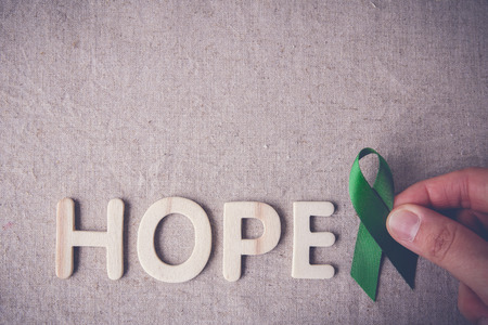 gastroparesis: fingers holding Green Ribbon with HOPE wooden word, cancer awareness, Liver, kidney cancer awareness
