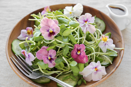Sunflower sprouts, cucumber and edible flowers salad on wooden bowl