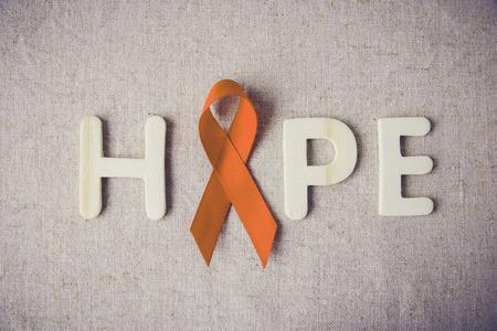 leucemia: Cintas de color naranja y carta de HOPE en el fondo de tonificación, la conciencia de la leucemia, día de la conciencia lesión del uno mismo, conciencia de la esclerosis múltiple