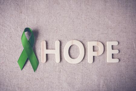 health awareness: Lime Green Ribbon with HOPE wooden word,Lyme disease, Mental health awareness Stock Photo