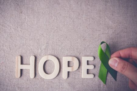 lyme: fingers holding Lime Green Ribbon with HOPE wooden word,Lyme disease, Mental health awareness