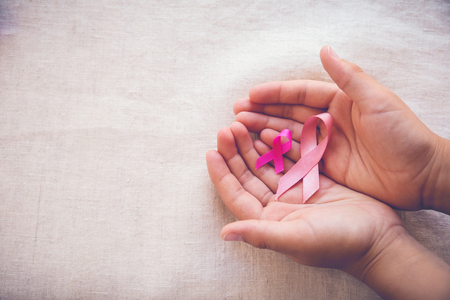 Hands holding Pink Ribbons toning background, Breast cancer awareness and Abdominal cancer awareness Stock Photo
