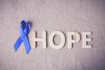 colorectal cancer: Blue ribbon with HOPE word, toning background, Colon Cancer, Colorectal Cancer, Child Abuse awareness