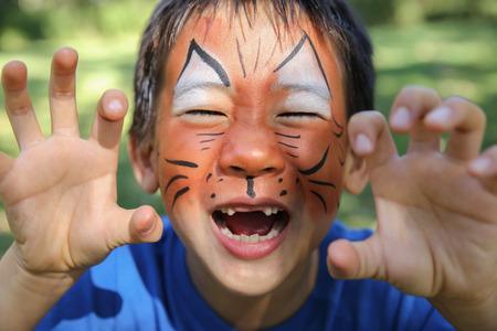 Jonge jongen met plezier schminken als een tijger Stockfoto