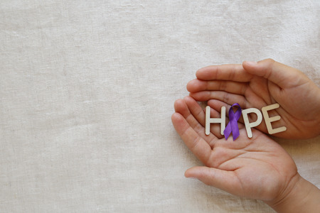 Hands holding HOPE with Purple ribbon, copy space background, Alzheimers disease, Pancreatic cancer, Epilepsy awareness, Hodgkins Lymphoma awareness
