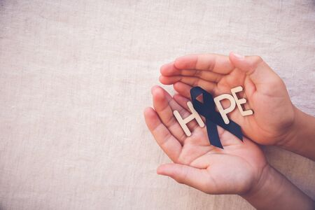 HOPE word with black ribbon on hands, for Skin cancer awareness, Melanoma Awareness,Narcolepsy Awareness and Mourning Stock Photo