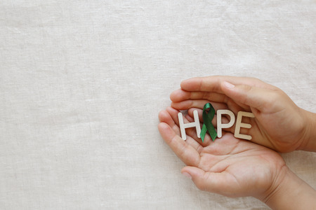Green Ribbon with HOPE wooden word on hands, Liver cancer awareness, kidney cancer awareness Archivio Fotografico