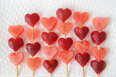brochetas de frutas: heart shape strawberry and watermelon fruit skewers on white plate, fun food art for Valentines day