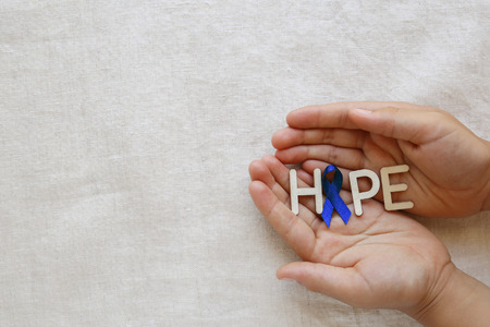 colorectal cancer: HOPE with Blue ribbon on hands, Colon Cancer, Colorectal Cancer, Child Abuse awareness Stock Photo