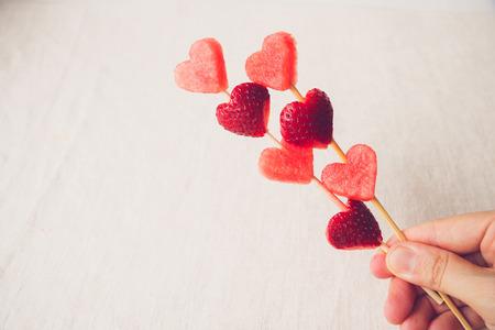brochetas de frutas: mano que sostiene la fresa en forma de corazón y sandía brochetas de fruta