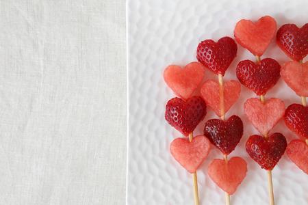 brochetas de frutas: la forma del corazón de la fresa y de la fruta de la sandía brochetas en un plato blanco
