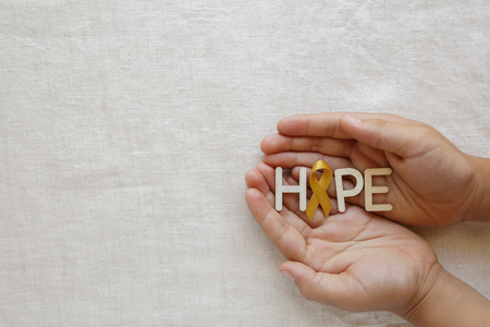 Hope with yellow gold ribbons on hands, Sarcoma Awareness, Bone cancer, Liver cancer, Bladder Cancer, childhood cancer awareness