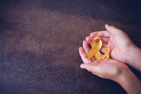 cintas de oro amarillo en las manos, conciencia del sarcoma, cáncer de hueso, cáncer de hígado, cáncer de vejiga, conciencia del cáncer de la niñez