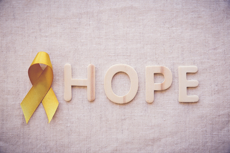 yellow gold ribbon with HOPE letters, Sarcoma Awareness, Bone cancer, Liver cancer, Bladder Cancer, childhood cancer awareness Stock Photo