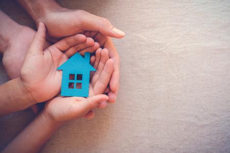 Mani del bambino e dell'adulto che tengono concetto di casa della casa, della casa di famiglia e del bene immobile Archivio Fotografico - 82818717