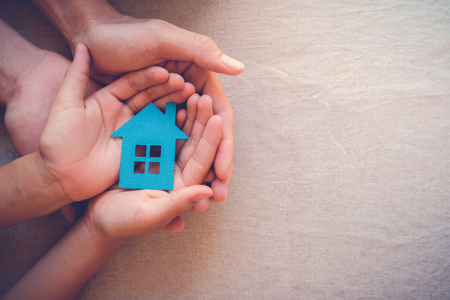 Adult and child hands holding paper house, family home and real estate concept