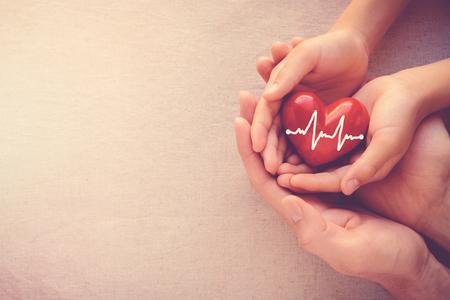 donacion de organos: manos de adulto y niño con corazón rojo con cardiograma, concepto de salud y amor de familia