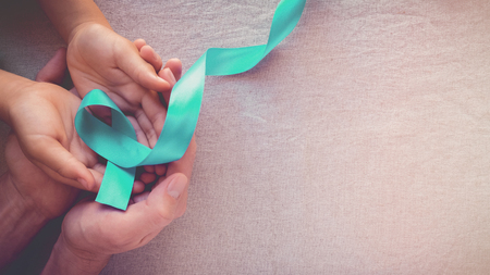 Adult and child hands holding Teal Ribbon, toning panoramic banner background, Ovarian Cancer, cervical Cancer, Kidney Cancer and sexual assault awareness Stock Photo
